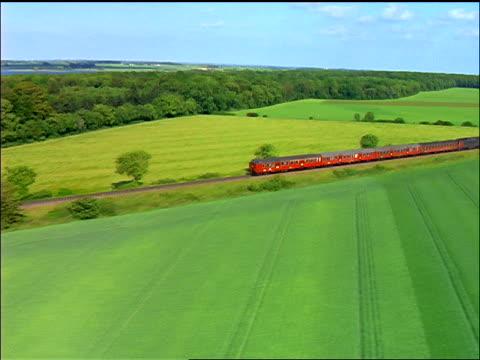 stockvideo's en b-roll-footage met aerial red train going through green countryside / gabense, falster, denmark - forensentrein