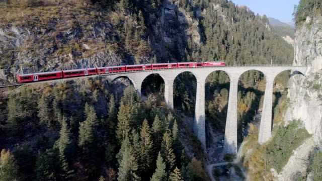 red train landwasser viaduct tunnel on bernina pass glacier express in switzerland - locomotive stock videos & royalty-free footage