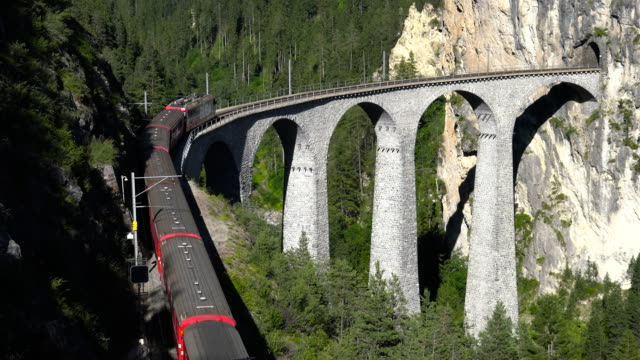 red train over stone bridge in the mountains - railway bridge stock videos & royalty-free footage