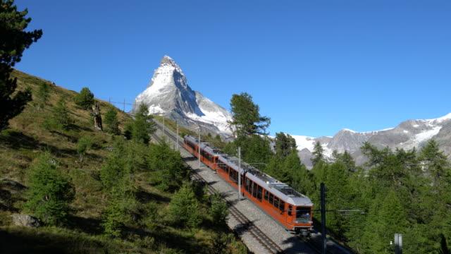 red train under the matterhorn - passenger train stock-videos und b-roll-filmmaterial