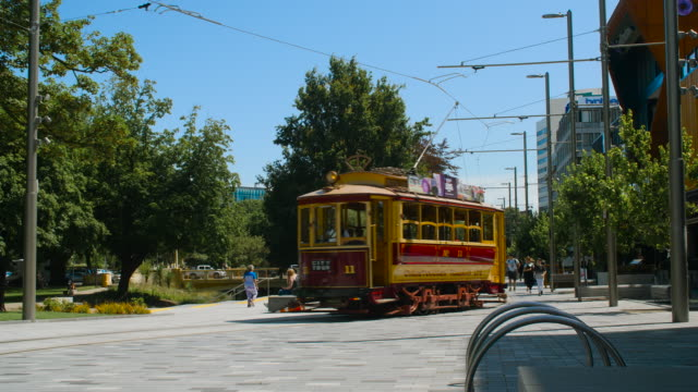 a red tram taking a city tour passes by on the terrace, christchurch - カンタベリー点の映像素材/bロール