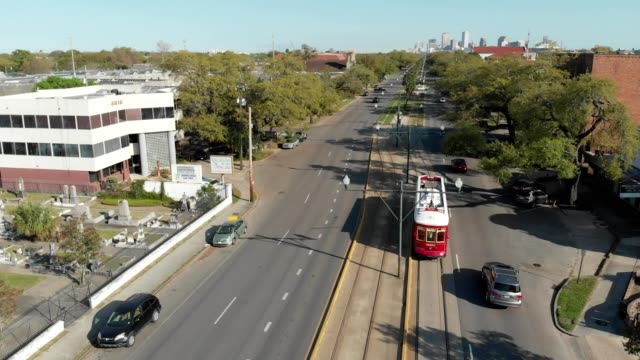 a red trolley heads towards new orleans french quarter in louisiana - new orleans stock videos & royalty-free footage
