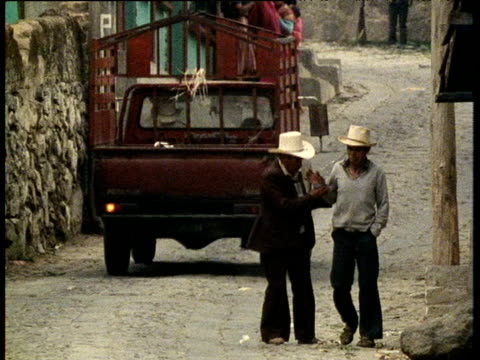 red truck drives past two men one struggles to help intoxicated man guatemala - guatemala stock videos & royalty-free footage