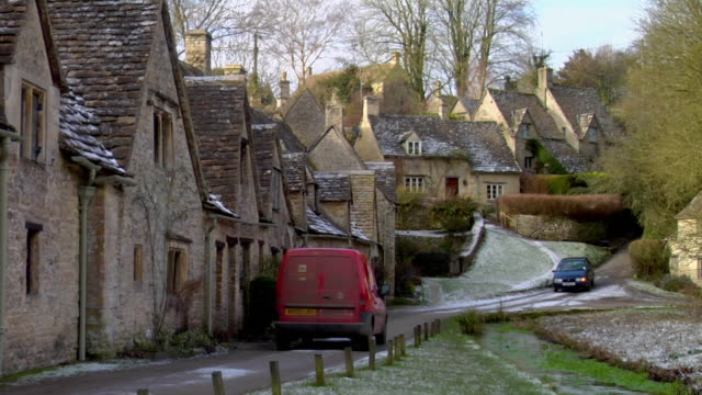 ws red van moving on road by row of houses / arlington row, bibury, uk - landhaus stock-videos und b-roll-filmmaterial