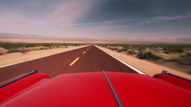 a red vintage cadillac drives along a desert highway. - collector's car stock videos and b-roll footage