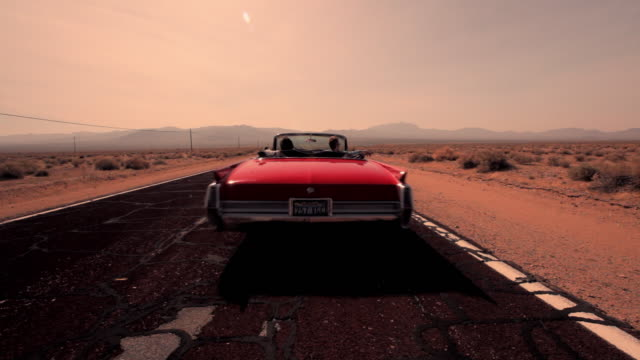 A red vintage convertible drives down a desert highway.