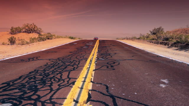 a red vintage convertible travels over patched cracks on a desert highway. - collector's car stock videos and b-roll footage