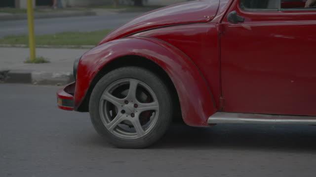 red volkwagen beetle driving down street - beetle stock videos & royalty-free footage