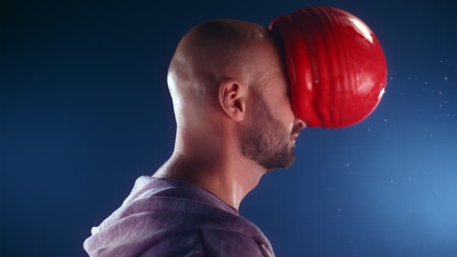 slo mo ld red water filled balloon hitting a man in the face without popping - human face stock videos & royalty-free footage