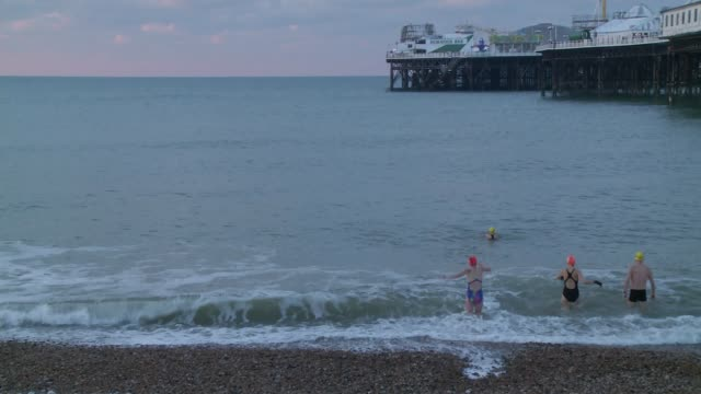 vídeos de stock e filmes b-roll de red weather warning issued in scotland / north of england badly hit england east sussex brighton swimmers walking across snow covered beach swimmers... - east sussex