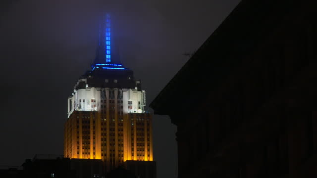 A red, white and blue Empire States Building at night, fog and clouds float behind.