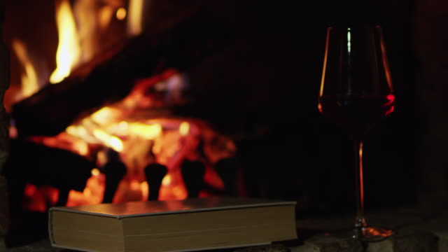4K Red wine and book by cozy fireplace, slow motion