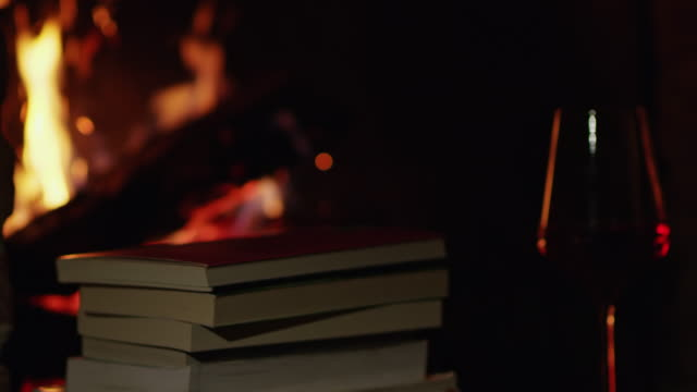 4K Red wine and stack of books by cozy fireplace, slow motion