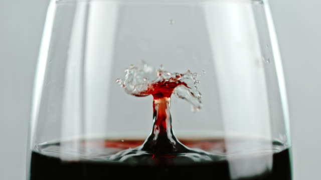 SLO MO Red wine dripping into a glass