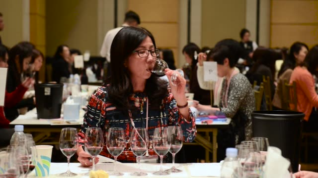 red wine is poured into a glass for judging at the 4th sakura japan women's wine awards 2017 the international wine competition judged by female wine... - giudizio video stock e b–roll