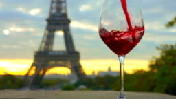 Red wine is poured into a glass.The Eiffel Tower