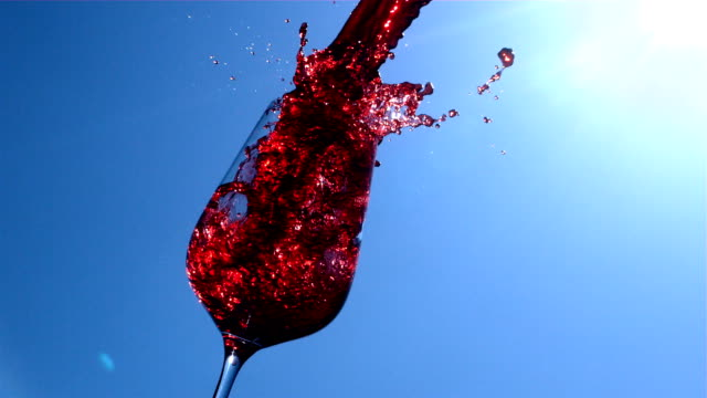 red wine is pouring in to a glass with blue sky and sunshine on background in slow motion - blue glass stock videos and b-roll footage