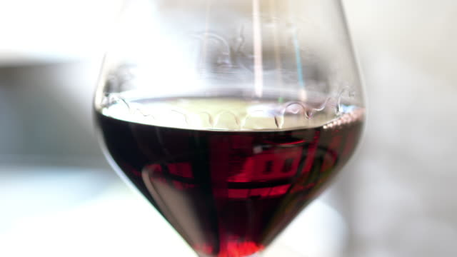 vidéos et rushes de red wine moving in a glass after being placed on table. - anorexie nerveuse