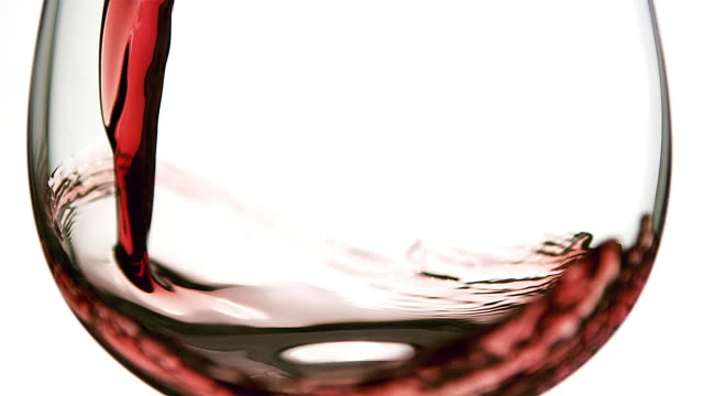 ECU SLO MO Red wine pouring into glass against white background / Vieux Pont, Normandy, France