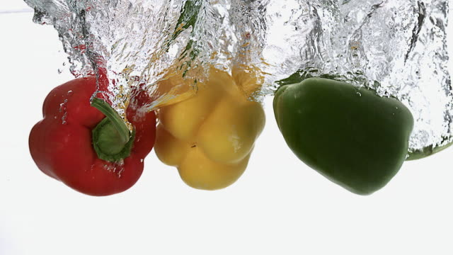 MS SLO MO Red, yellow and green capsicum falling into water against white background / Vieux Pont, Normandy, France