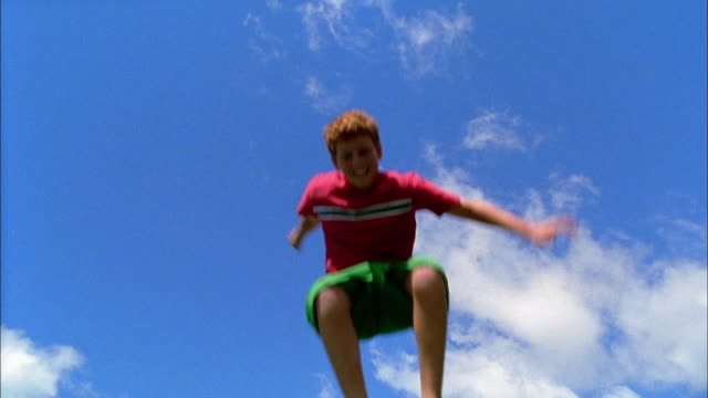 stockvideo's en b-roll-footage met a red-haired boy jumps on a trampoline. - trampoline