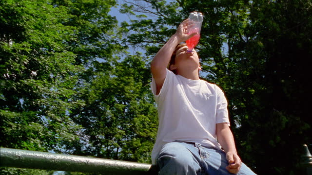 A red-haired boy sits on a fence drinking soda pop.