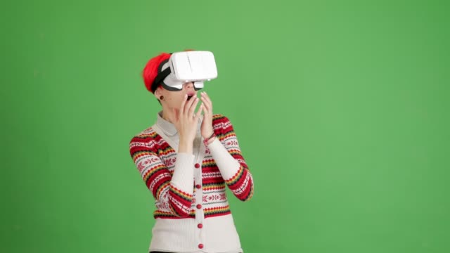 red-haired girl gets scared with virtual reality glasses on a green background - blouse stock videos & royalty-free footage