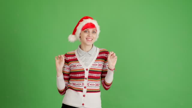 red-haired girl in a santa hat dancing on a green background - blouse stock videos & royalty-free footage