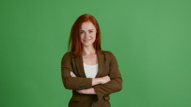 Red-haired woman businessman on a green background