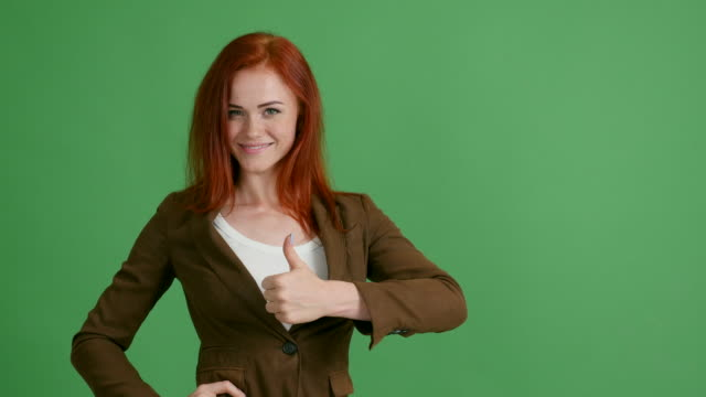 red-haired woman businessman shows copy space on green background - redhead stock videos and b-roll footage