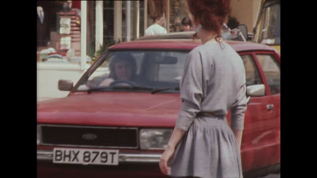 vídeos y material grabado en eventos de stock de a red-haired woman crosses a london road wearing 1980s fashion - falda