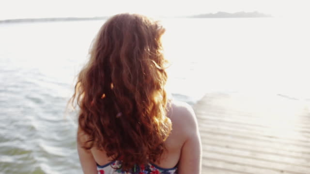red-haired woman on the lakefront smiling and flirting - winken stock-videos und b-roll-filmmaterial