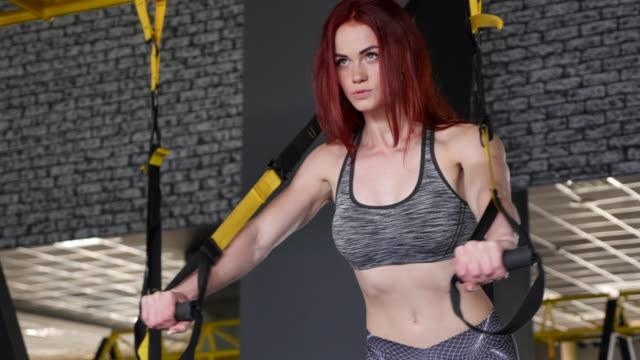 vídeos y material grabado en eventos de stock de mujer de gimnasio redhead entrenamiento con trx cintas de fitness - animadora