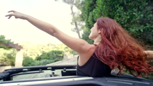 redhead girl having fun in a suv with sun roof - human hair stock videos & royalty-free footage