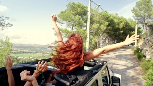 Redhead girl having fun in a SUV with sun roof