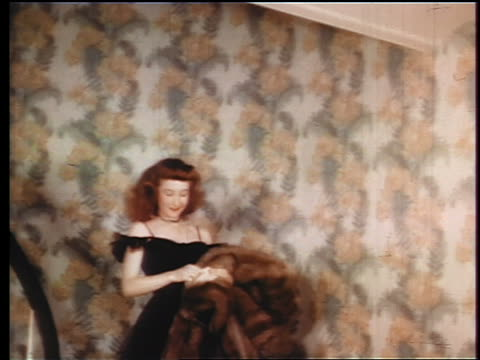 1945 red-head girl in black dress coming downstairs to greet date / puts on fur coat / industrial