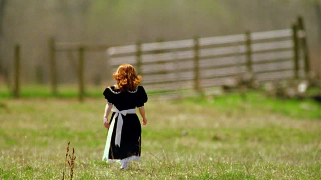rear view redhead girl in black dress running, walking + looking around in green field / fence in background - black dress stock videos & royalty-free footage
