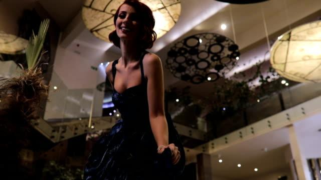 stockvideo's en b-roll-footage met roodharige dame in blauwe jurk in de lobby van het hotel - jurk