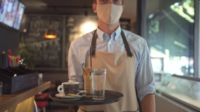 vídeos y material grabado en eventos de stock de camarero pelirrojo sosteniendo una bandeja con el pedido del cliente listo para servirlos mientras usa máscara protectora para la cara - camarero