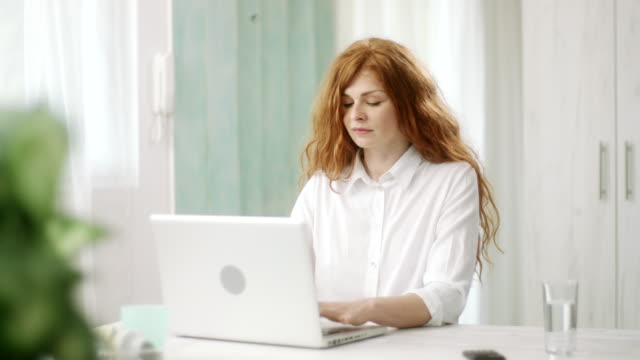 Redhead woman typing on laptop