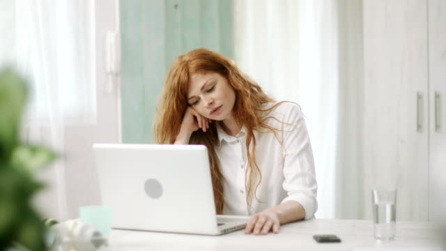 Redhead woman using laptop and affirmatively nodding while looking at camera