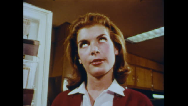 vídeos de stock e filmes b-roll de 1966 red-headed teenage girl rolls her eyes in the kitchen - displeased