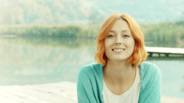 redheaded woman looking at camera and smiling - one young woman only stock videos & royalty-free footage