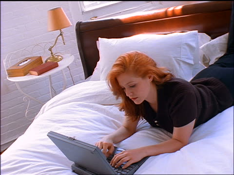 canted handheld redheaded woman lying on stomach on bed types on laptop computer - ヘッドボード点の映像素材/bロール