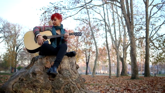 redheaded woman playing acoustic guitar sitting on a tree stump - daydreaming stock videos & royalty-free footage