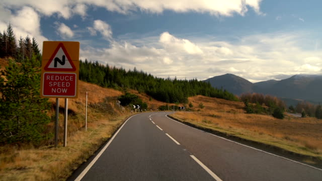 reduce speed sign in the beautiful autumn road trip in scotland - scottish highlands stock videos & royalty-free footage