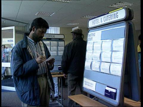 Redundancy TX Job Centre SEQ Men looking at latest vacancies board