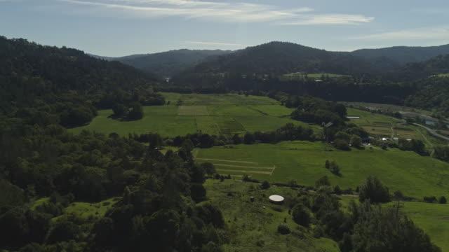 vídeos de stock, filmes e b-roll de redwoods em montes e em umas explorações agrícolas pequenas ao longo da estrada do redwood 101 perto de garbeville, califórnia, eua no dia de mola ensolarado. vídeo aéreo do zangão com o movimento dianteiro e inclinando-para baixo da câmera. - sequoia sempervirens