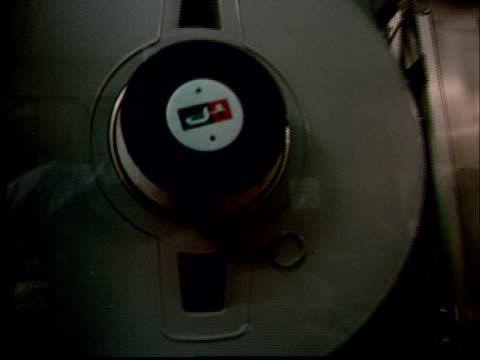 1970 ms pan reel-to-reel tapes spinning in large machine / ms man operating machine/ pan man walking away as co-worker writes at desk - machinery stock videos & royalty-free footage