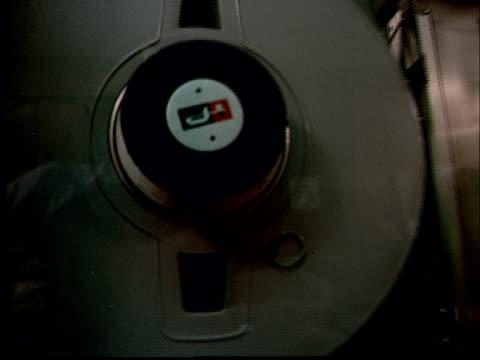 1970 ms pan reel-to-reel tapes spinning in large machine / ms man operating machine/ pan man walking away as co-worker writes at desk - maskineri bildbanksvideor och videomaterial från bakom kulisserna